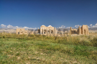 Ruins of ancient temple on green grasslands in Kyrgyzstan