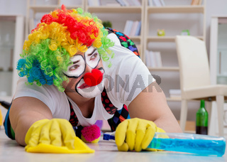 The funny clown doing cleaning at home