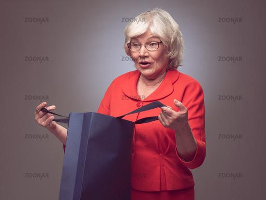 Shopping senior woman surprised