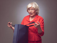 Shopping senior woman surprised