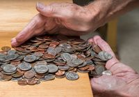 Hands scooping up loose USA change with mixed coins on wooden table