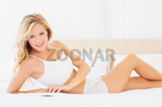 Sexy blonde woman lying on bed smiling at camera