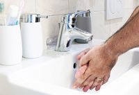 a man washing his hands in a white ceramic sink