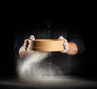 chef a man in a black uniform holds a round wooden sieve in his hands and sifts white wheat flour