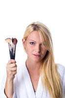 Young woman with makeup brush in hand