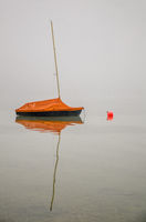 Moored Sailboat in the Fog With Reflection