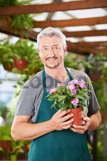 Gärtner mit Blume im Blumenladen