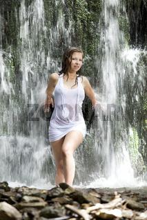 Nasse junge Frau im Wasserfall