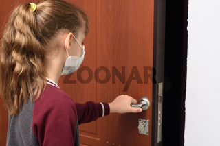 The girl in the respirator opens the front door to go outside