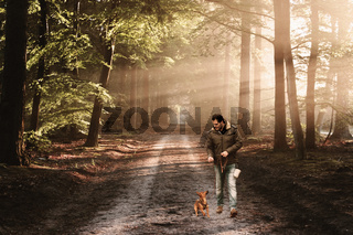 Man and his dog walking on a track in the forest. Hiking, dog school and outdoor activity concept.