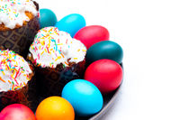 Colored painted eggs and Easter cake on a plate on a white background. Easter. Religious holiday.