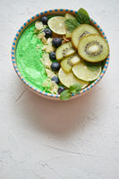 Green smoothie or yogurt bowl. With fresh kiwi, blueberries, lime and almond flakes