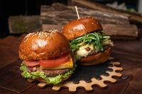 Two amazing fresh beef burgers served with french fries, one with fried walnuts and grilled cheese on a decorative wooden part of simple mechanism. Restaurant concept. Fast food, street food concept