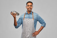 indian barman in apron with cocktail shaker