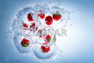 Raspberries splashing into clear water, view from top