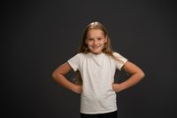 Bossy little girl of 8,10 years put her hands sideways looks questioningly at the camera wearing white t shirt isolated on dark grey or black background