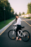 Beautiful girl posing at white bicycle. Walk in nature.