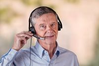Senior man using headset to communicate with team or customers