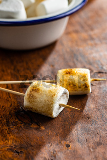 Grilled sweet marshmallows on wooden table.