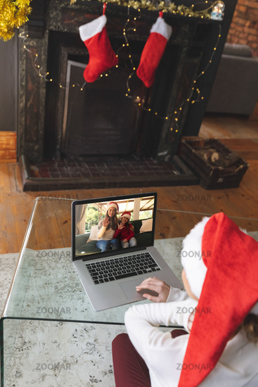 Rear view of woman in santa hat having a videocall with woman and daughter in santa hats waving on l