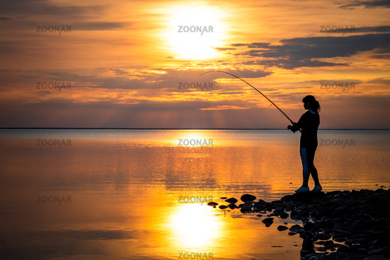 Woman fishing on Fishing rod spinning at sunset background.