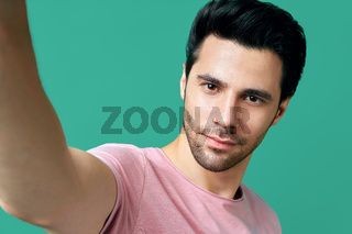 Close up portrait of handsome man taking selfie