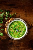 Vegan soup. Green cream soup, overhead shot on a dark rustic wooden background