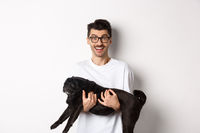 Happy young man in glasses holding black pug pet and staring at camera amused, smiling cheerful, standing over white background