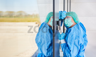Arzt in Schutzkleidung lehnt erschöpft an Tür wegen Stress und Erschöpfung