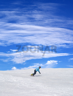 Snowboarder on ski slope and blue sky with clouds