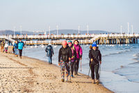 Poland, Sopot, February 9, 2020. People at beach in Sopot. Crowd on Beach During Winter. enjoying day in sunny winter near sea. People walking along on Baltic sea, surf line on warm sunny winter day