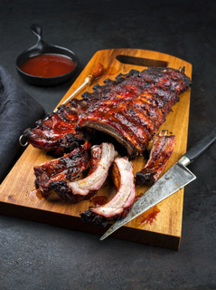 Barbecue pork spare ribs St Louis cut with hot honey chili marinade as closeup on an modern design wooden cutting board