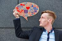 Geschäftsmann hält Sprechblase mit Icons