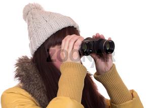 Junge Frau mit Mütze schaut durch ein Fernglas