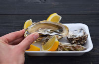 Woman eating fresh open oysters with lemon