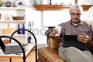 Closeup of a man working from home during the Covid-19 lockdown. Taking a coffee break using his tablet computer.