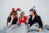 Smiling Female Models Holding Wine Glasses And Enjoying Pajamas Party.