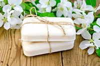 Soap with white flowers of apple on board