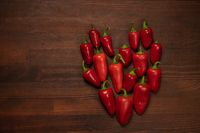 Fresh heart of chillies or peppers and capsicums or bell peppers. Sweet bell, paprika, cayenne, chilli, Hungarian wax pepper, isolated on wooden table background. Valentine day concept. Copy space