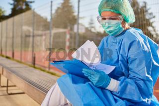 Klinik Mitarbeiter studiert Kontaktverfolgung Liste von Besuchern