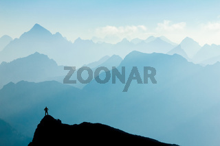 Man reaching summit after climbing and hiking enjoying freedom and looking towards mountains silhouettes panorama in early Morning.