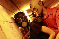 Married couple in gas masks in a tunnel