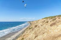 Parachuters over San Diego California landscape of blue ocean and rocky mountain