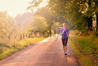 Sportliche Frau läuft auf einer ländlichen Straße