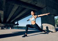 Young sporty woman doing yoga asana Warrior I Pose outdoors under industrial bridge