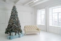New Year studio interior. Christmas tree is decorated with balloons, with Christmas gifts under it. White sofa stands under the window and Christmas tree. High quality photo