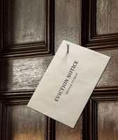 Envelope nailed to wooden door with eviction notice