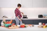 Pretty woman cooking dinner for big family stirring dish in the pot standing sideways to the camera. Healthy food living. Healthy lifestyle. Selective focus on vegetables