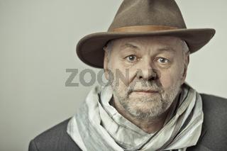 Älterer Mann mit Bart und Hutkopf schaut fröhlich in die Kamera