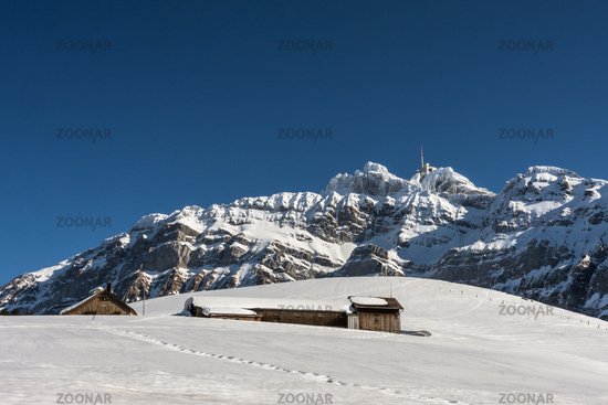 Small mountain huts on an alp in front of the Saentis massif in winter, Switzerland